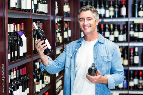 Photo Smiling man holding bottles of wine
