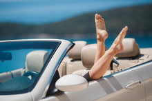 Slender Women's Legs Look Out Of Car Window.