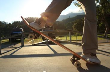 skateboarder legs at sunrise skatepark
