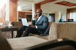 Happy businessman in hotel lobby using cell phone and laptop
