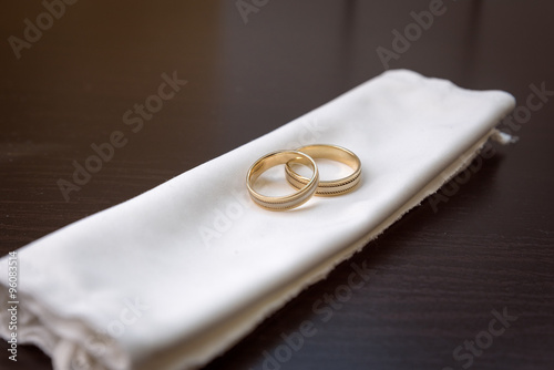 Two Gold Wedding Rings Lying On A White Cloth On A Dark Background