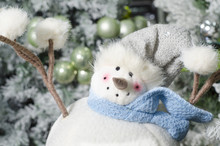 Closeup Of Cute Plush Snowman Toy And Decorated Christmas Tree In Background