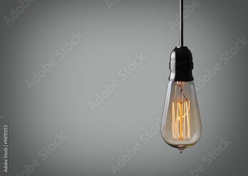 Photo  Vintage hanging light bulb over gray background