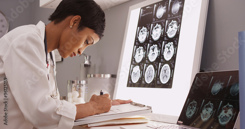 Fotografija  African medical woman reading x-ray results of a brain