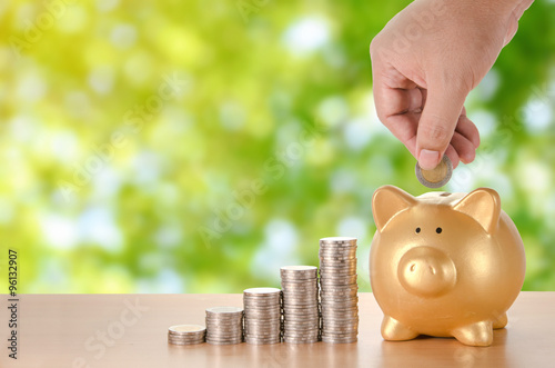 Fotografía  man hand with coins plan to saving money with gold piggy bank