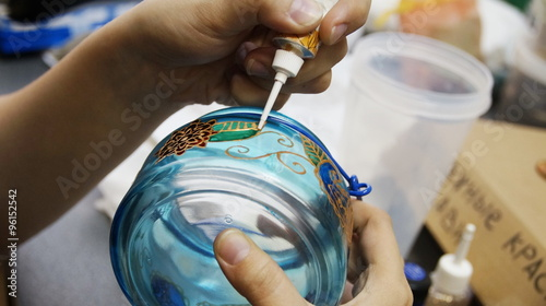 painting with stained glass paints and line paints on transparent blue glass jar