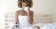 Attractive Woman With A Cup Of Coffee On The Bed