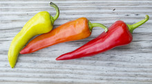 Three Brightly Colored Banana Chili Peppers Against An Old Weathered Wood Background.