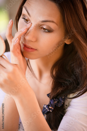 Aluminium Prints Manicure Young woman corrects make-up