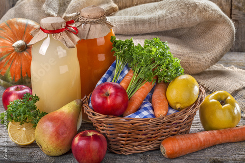 Fototapeta .Different bottles of juice with ripe fruits and vegetables on rustic table and in front of the linen background. obraz na płótnie