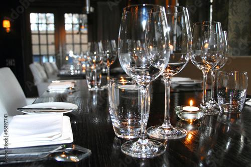 Door stickers Grocery sfeervol gedekte tafel met wijnglazen, borden en bestek in een restaurant
