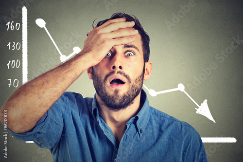Cuadros en Lienzo stressed shocked business man with financial market chart graphic going down