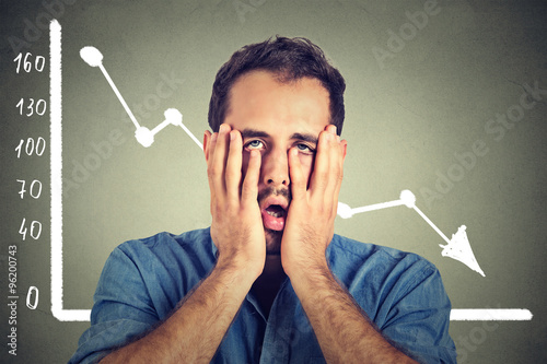 Cuadros en Lienzo frustrated stressed young man desperate with financial market chart graphic goin