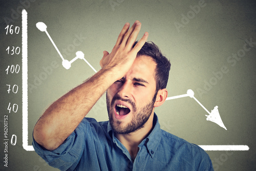 Fotomural frustrated stressed young man desperate with financial market chart graphic goin