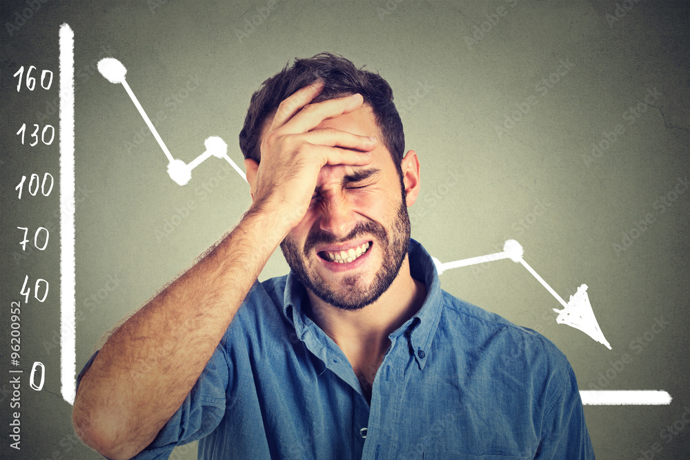 Fotografía frustrated stressed young man desperate with financial market chart graphic goin