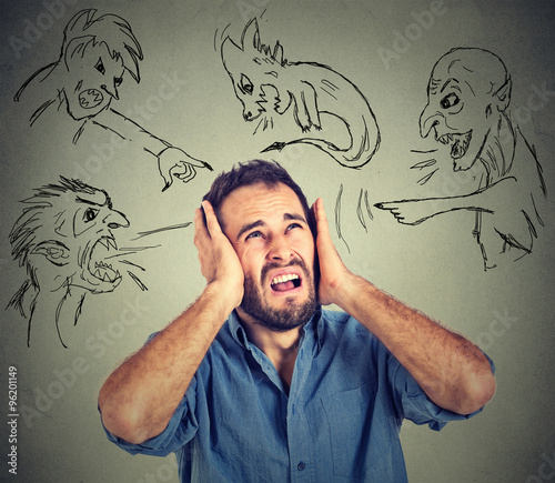 Fotografie, Obraz  Stressed young man covers his ears with his hands evil guys pointing fingers at