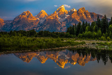 The Dramatic Colors Of The Grand Teton Mountains Reflecting In The Water On A Clear Summer Morning.