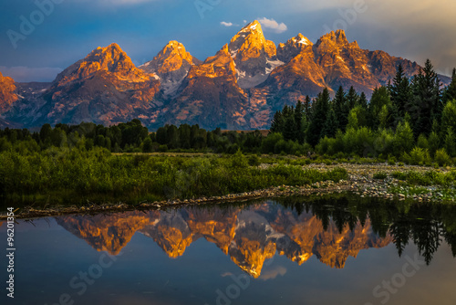 Fototapeta The dramatic colors of the Grand Teton Mountains reflecting in the water on a clear summer morning