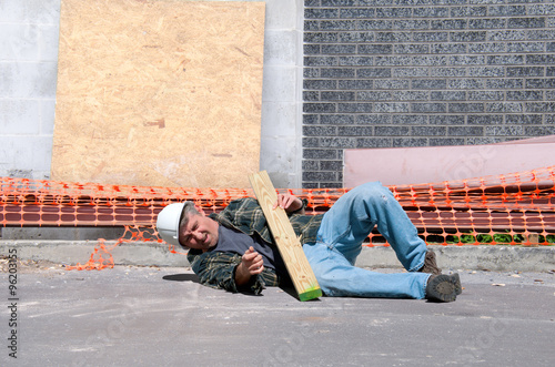 A fallen and injured construction worker in a hard hat laying on the ground at a Poster