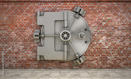 The metallic bank vault door on the brick wall. Concept of safet Canvas Print