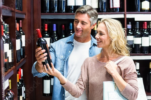 Smiling couple looking at bottle of wine Wallpaper Mural