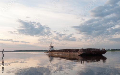Fotografia  Cargo ship against panorama of Severnaya Dvina river in sunset background