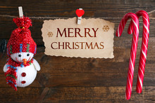 Greetings Merry Christmas Written On The Paper And Christmas Decorations With Candy On A Rope On A Wooden Brown Background