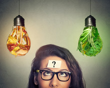 Woman Thinking Looking At Junk Food And Vegetables Shaped As Light Bulb