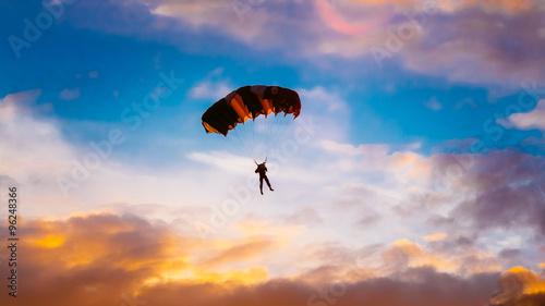 Obraz na płótnie Skydiver On Colorful Parachute In Sunny Sunset Sunrise Sky
