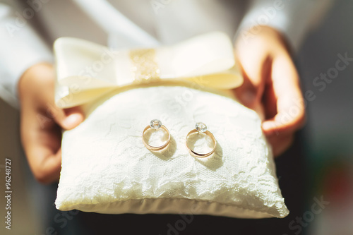 Photo boy holds a magnificent pair of shiny golden wedding rings on a