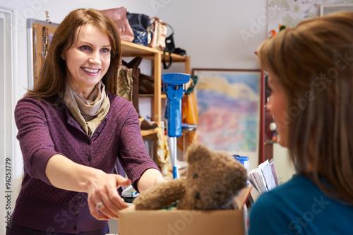 Plakat Kobieta darowizny niechcianych przedmiotów do sklepu charytatywnego