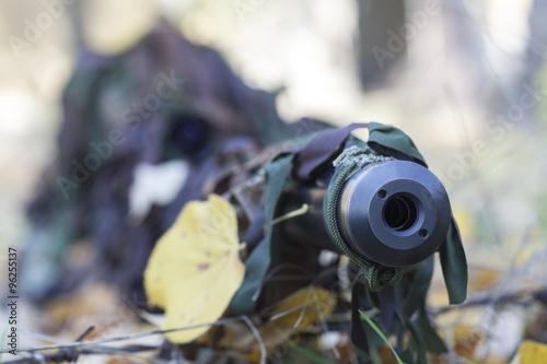 Fotografía  Centrarse en el cañón de un francotirador en uniforme de camuflaje