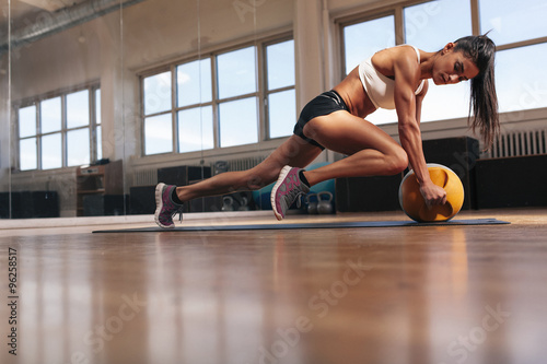 Muscular young woman doing workout at gym Canvas Print