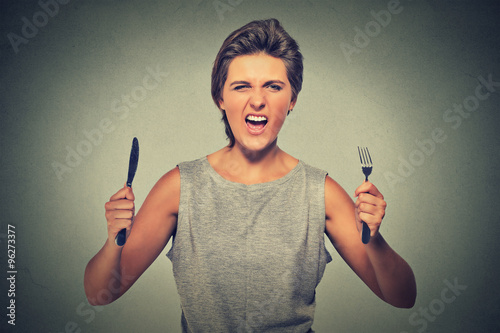 Valokuva  Portrait of a very hungry young woman screaming displeased