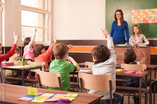 Children in elementary school are raised hand in clasroom Poster