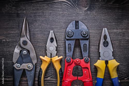 Sharp tin snips steel cutter pliers on wooden board Tableau sur Toile