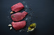 Leinwanddruck Bild - Raw marbled meat steaks with seasonings, black wooden surface
