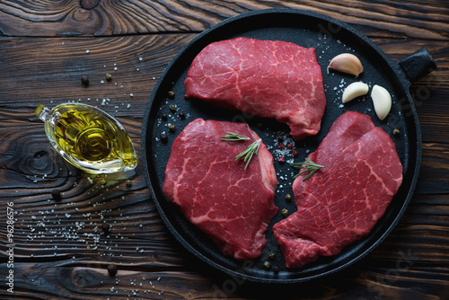 Fotografering  Top view of raw fresh black angus beef steaks in a frying pan