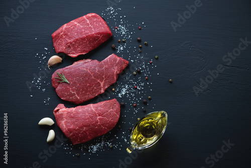 Fotografia  Raw marbled meat steaks with seasonings, black wooden surface