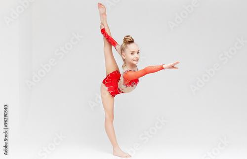 Tuinposter Gymnastiek Little girl in red dress doing standing split.
