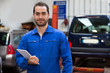 Young attractive mechanic working at the garage