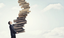 Man With Stack Of Books In Hands