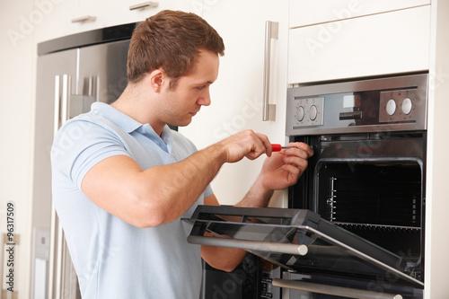 Fotografía  Man Repairing Domestic Oven In Kitchen