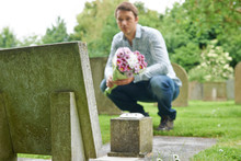 Man Placing Flowers By Headstone In Cemetery