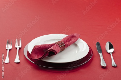 Photo  table setting with utensils plate and red cloth