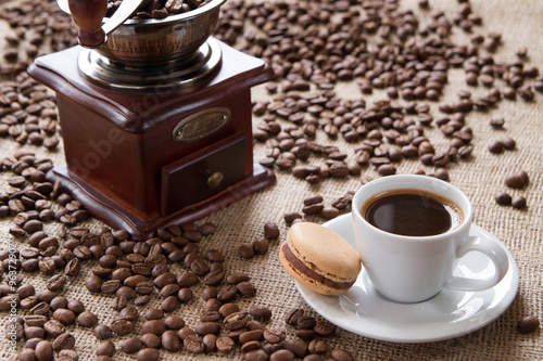 cup of coffee with macarons on a background coffee beans