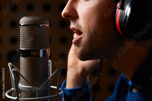 Male Vocalist Singing Into Microphone In Recording Studio Fototapeta