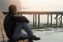 Man Sitting On Old Wooden Dock...