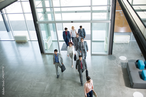 Group of professional business people walking in building.