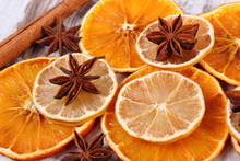 Slices Of Dried Lemon, Orange And Spices On Old Wooden Background